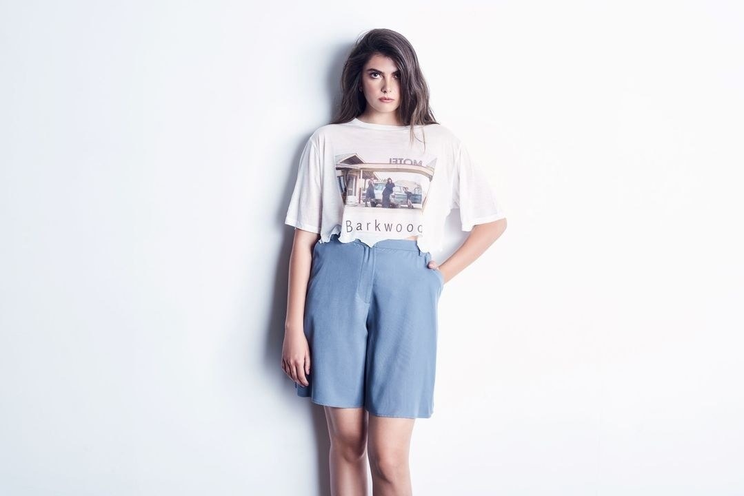 Model wearing the knee-length trousers in blue with a cropped t-shirt