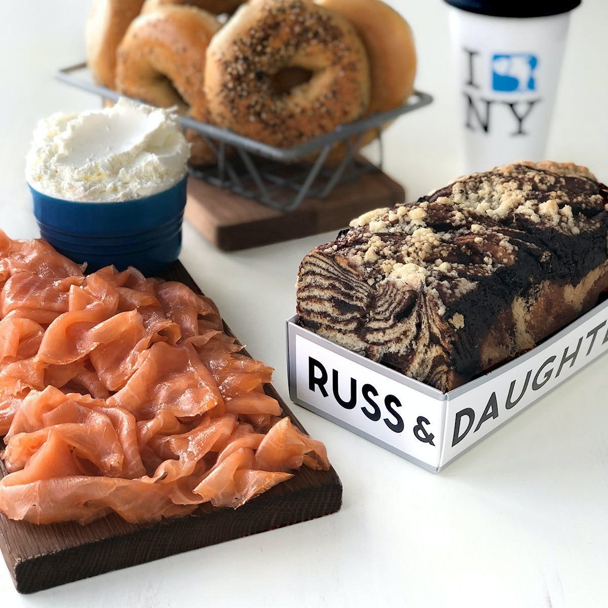 A cutting board topped with sliced lox, a box of chocolate babka, bagels, and cream cheese from Russ and Daughter's.