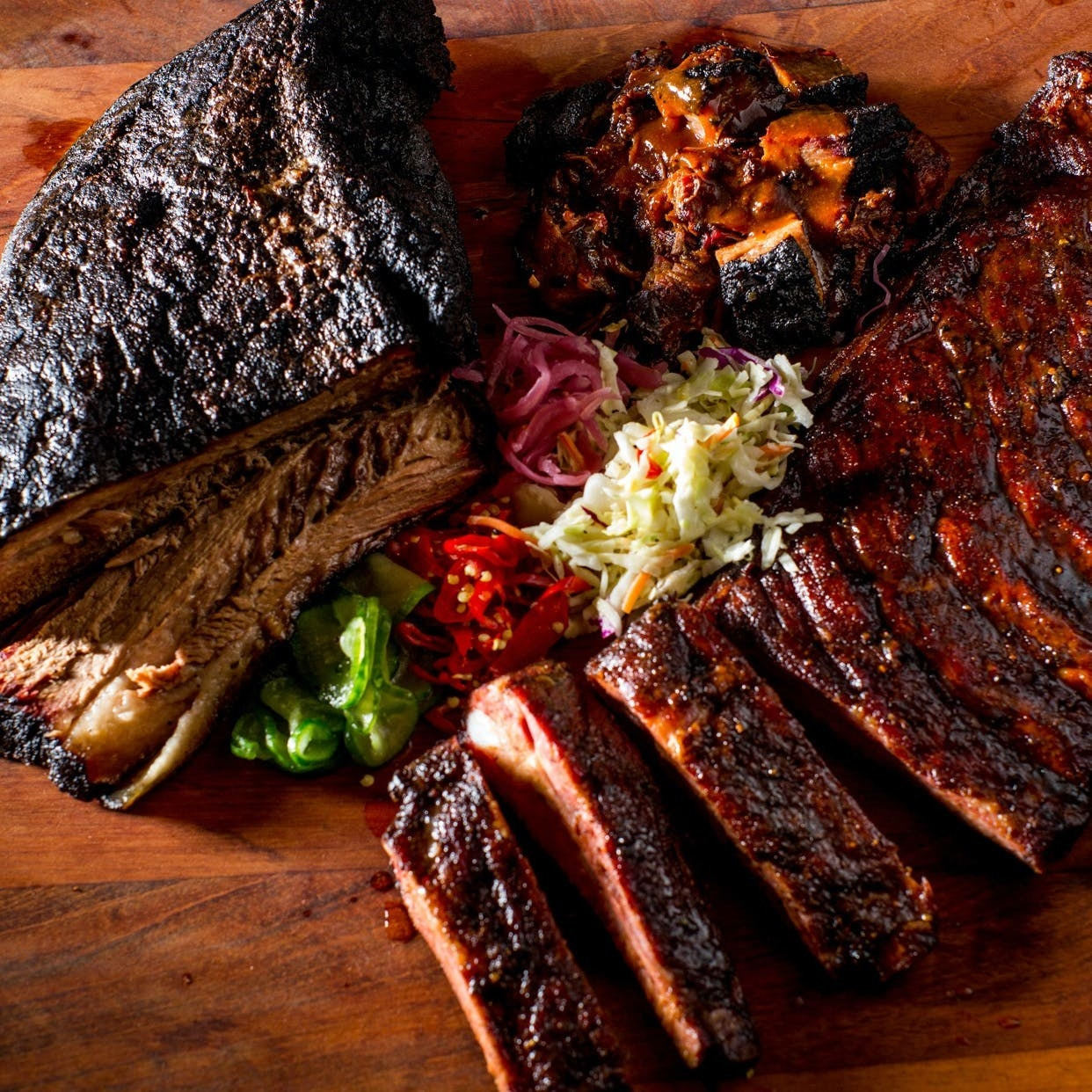 Ribs, brisket, burnt ends, coleslaw, onions, and peppers from a Mighty Quinn's sampler pack.