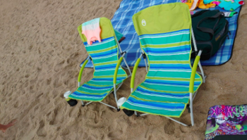 Reviewer's blue and green striped beach chairs lined up on the sand