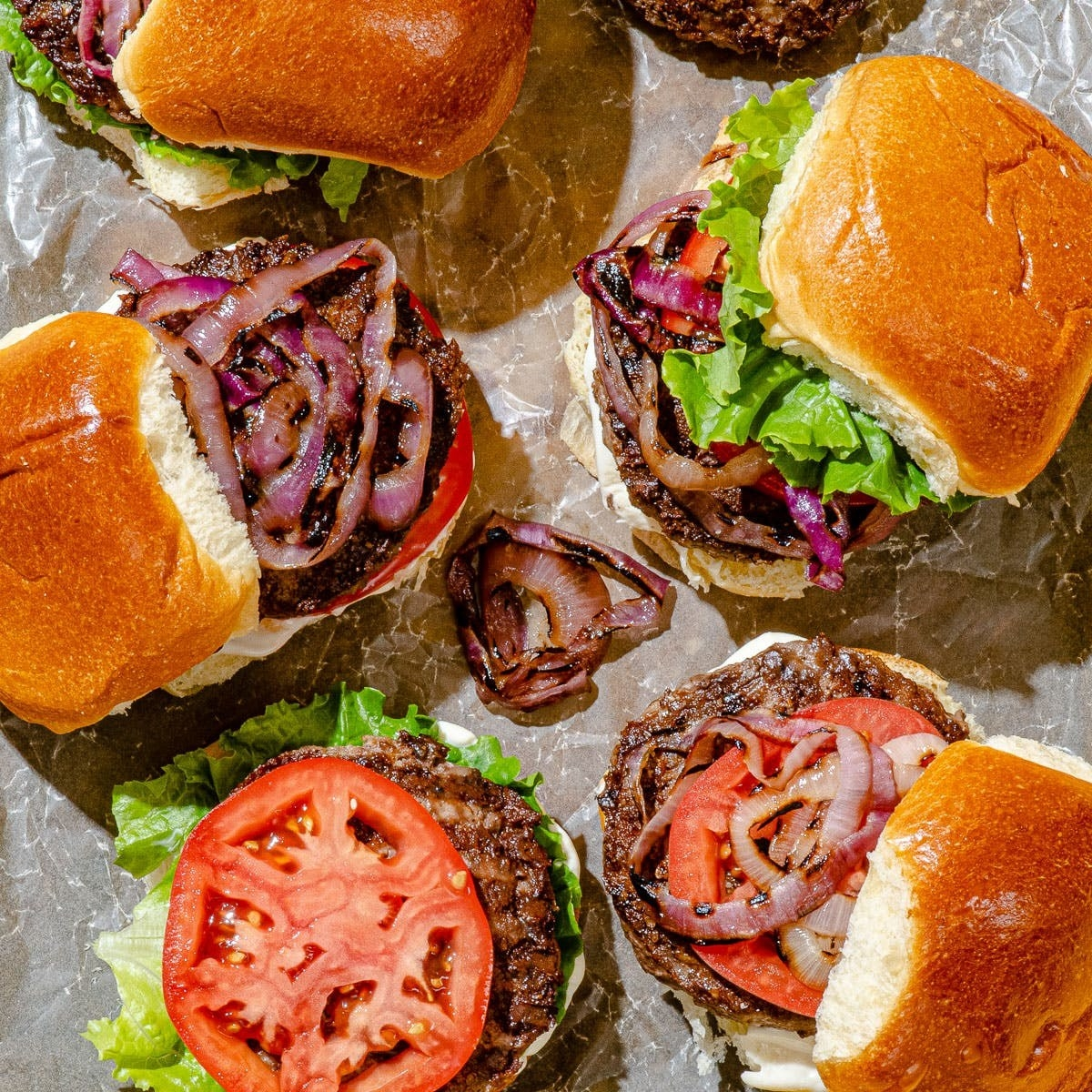 Five grilled hamburgers on buns with onions, tomato, and lattuce.