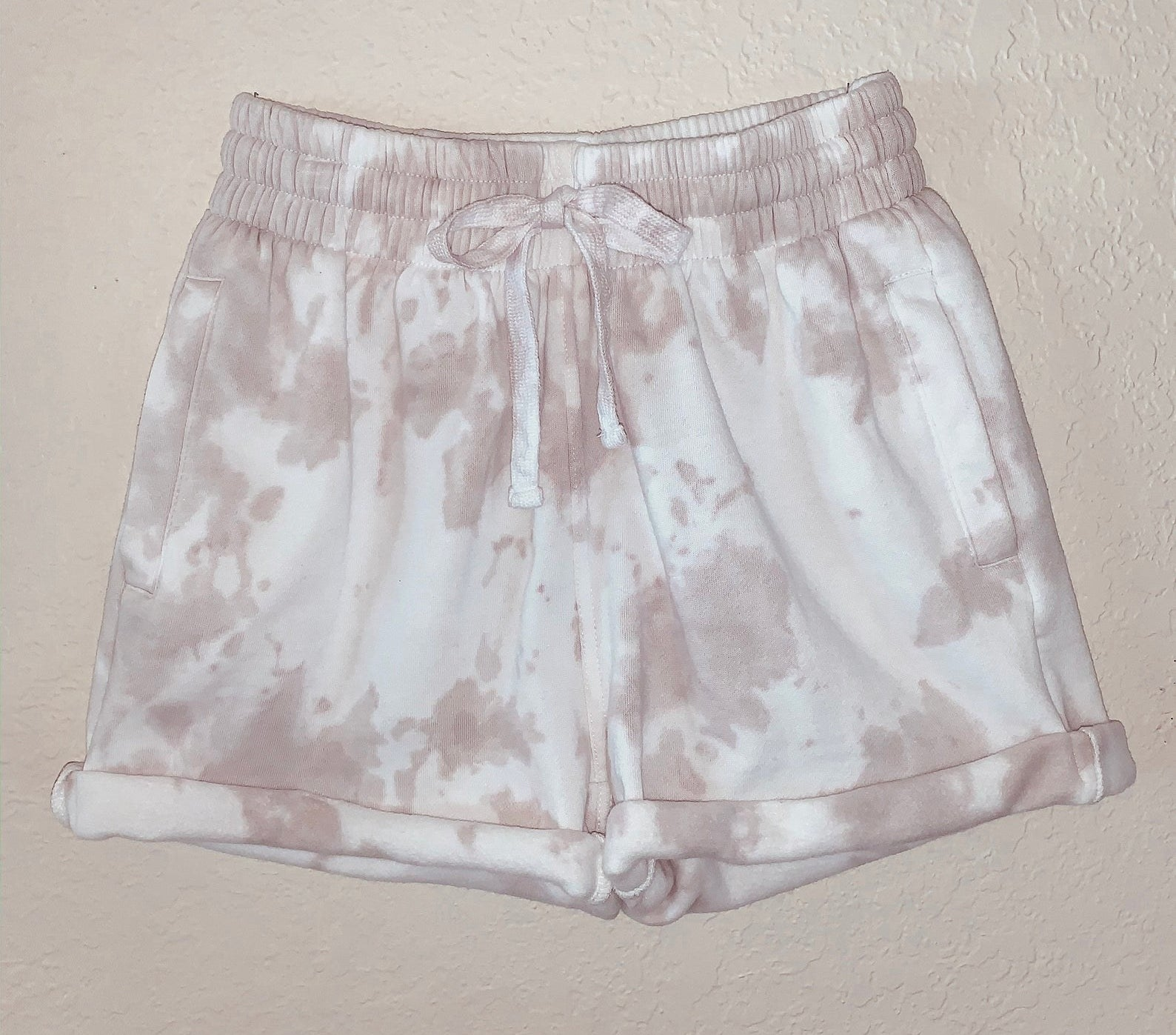 The shorts with a beige and white tie-dye pattern