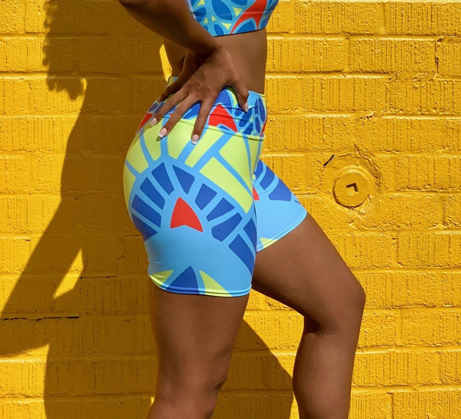 Model wearing the booty shorts in light blue with a dark blue, red, and yellow graphic pattern