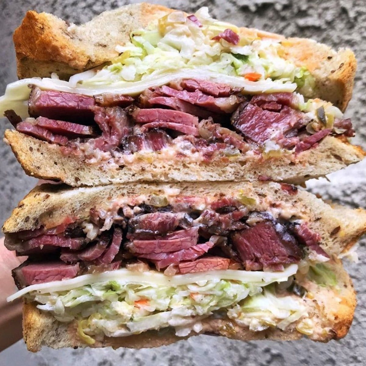 Two halves of a Langer's Original #19 on Jewish Rye bread, stuffed with pastrami, coleslaw, and mayo.