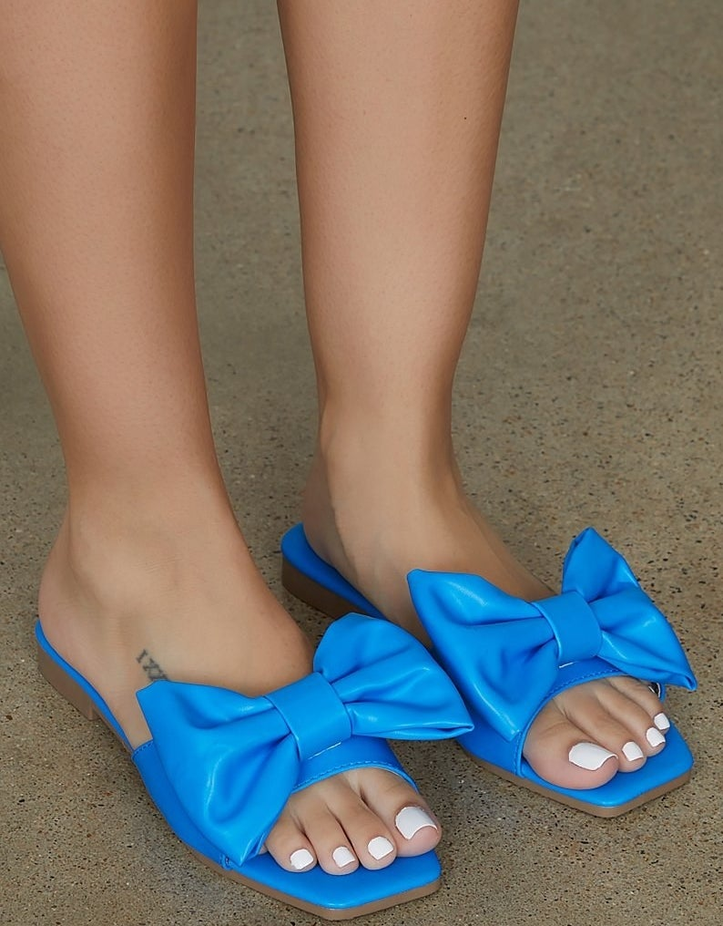 Feet wearing the bright blue sandals with oversized bows on the strap