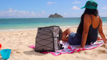 Same reviewer shows front side of the cooler, which has bungee detailing, while relaxing at the beach