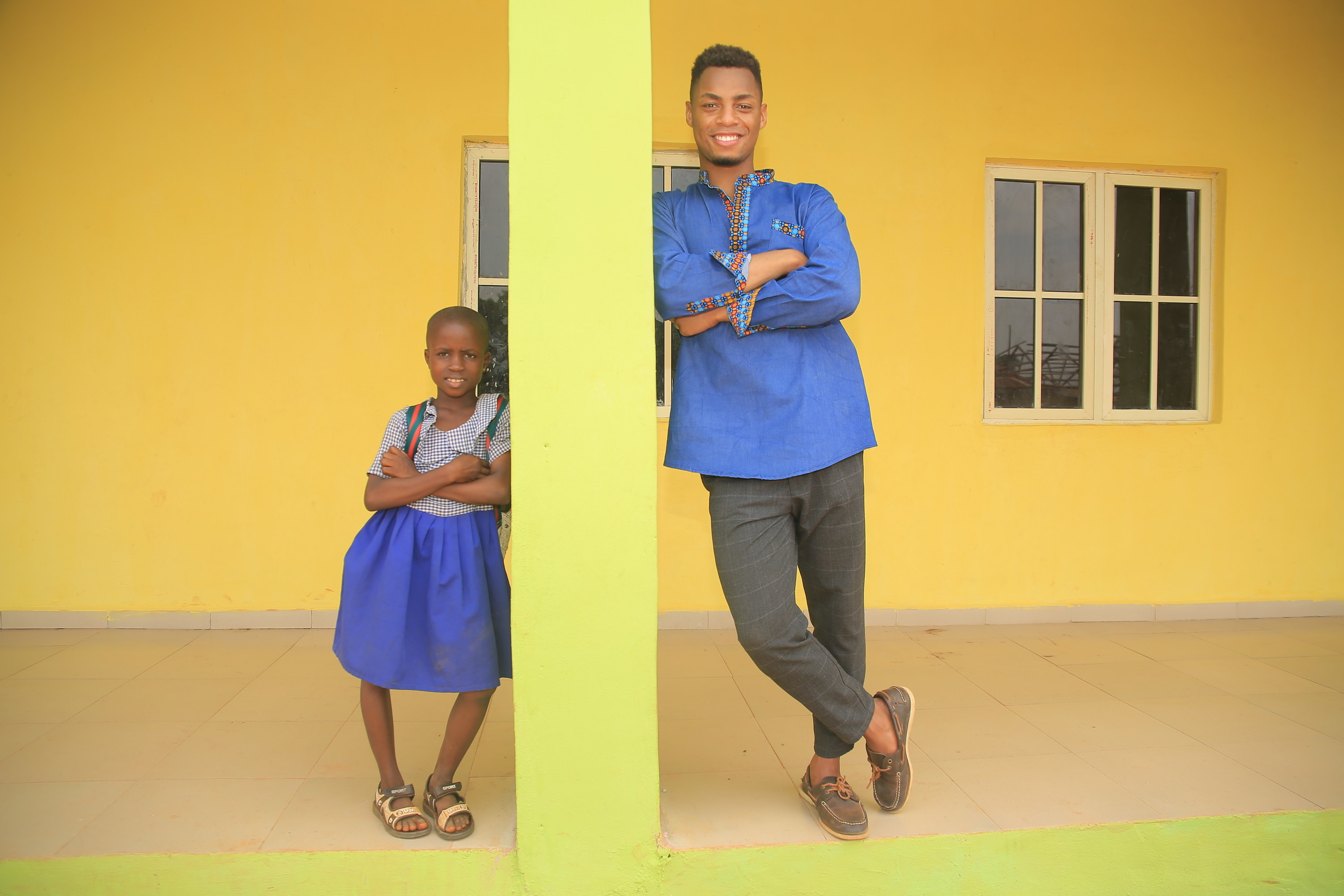 A young child (left) and Uyi Omorogbe (right) lean against a yellow pillar