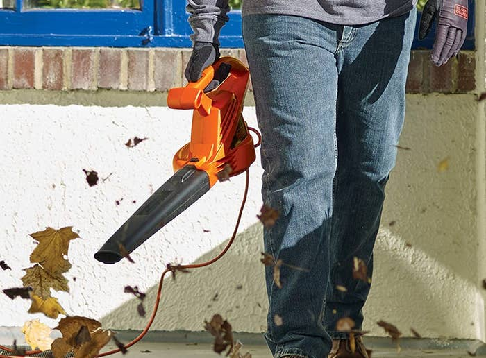 a model holding the leaf blower with an orange handle