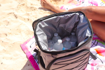 Reviewer shows open white cooler of water bottles while sitting on a beach blanket
