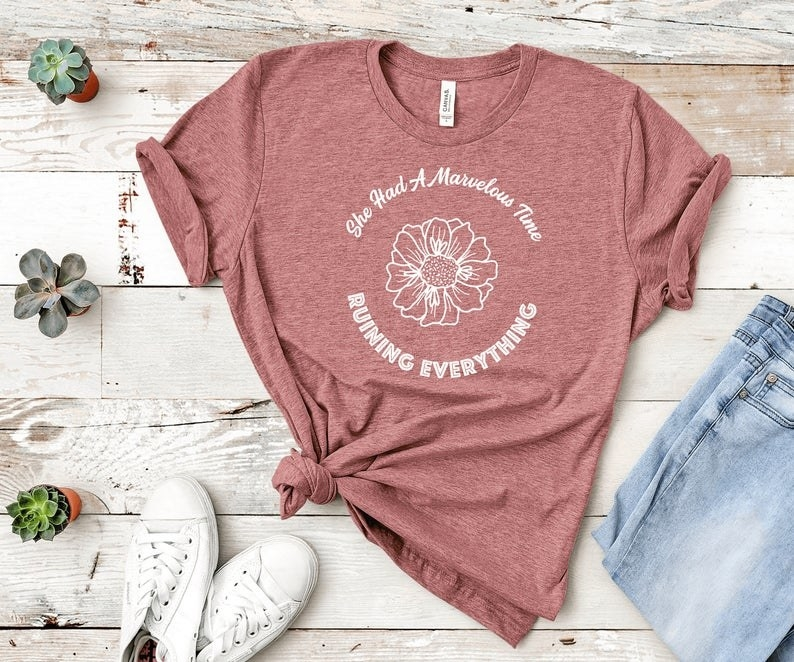 "The pale red short-sleeve tee, which has the words ""She had a marvelous time ruining everything"" printed in a circle around a flower design"