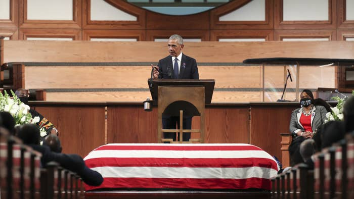 Barack Obama speaks from a lectern while standing above John Lewis's coffin, which is draped in a US flag