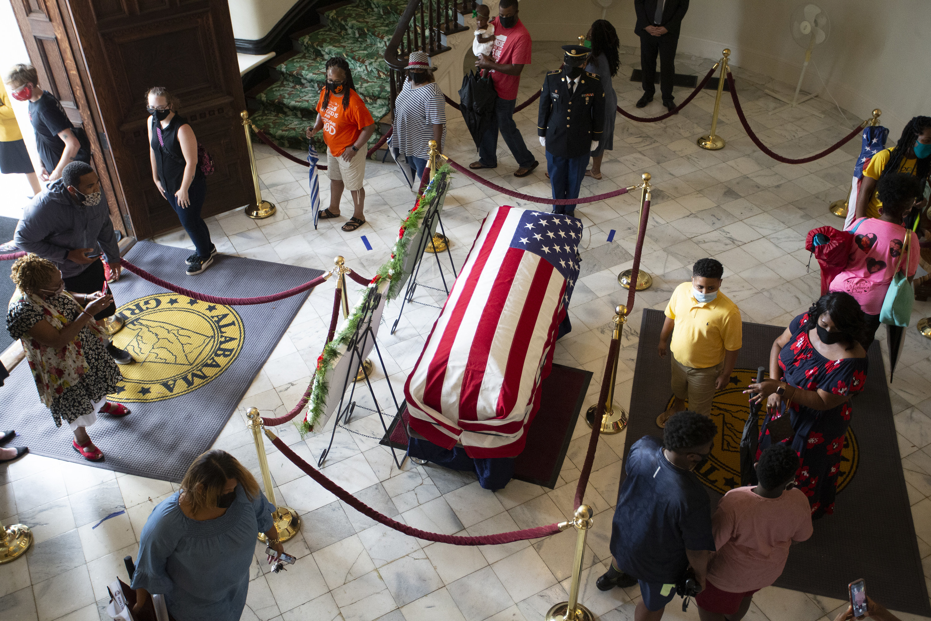 Visitors wearing masks walk around a casket, which is covered by a US flag and cordoned off by velvet rope barriers