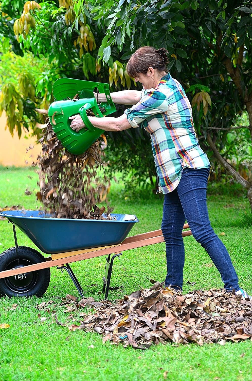 a model using the oversized plastic gloves to pick up massive piles of leaves without a rake