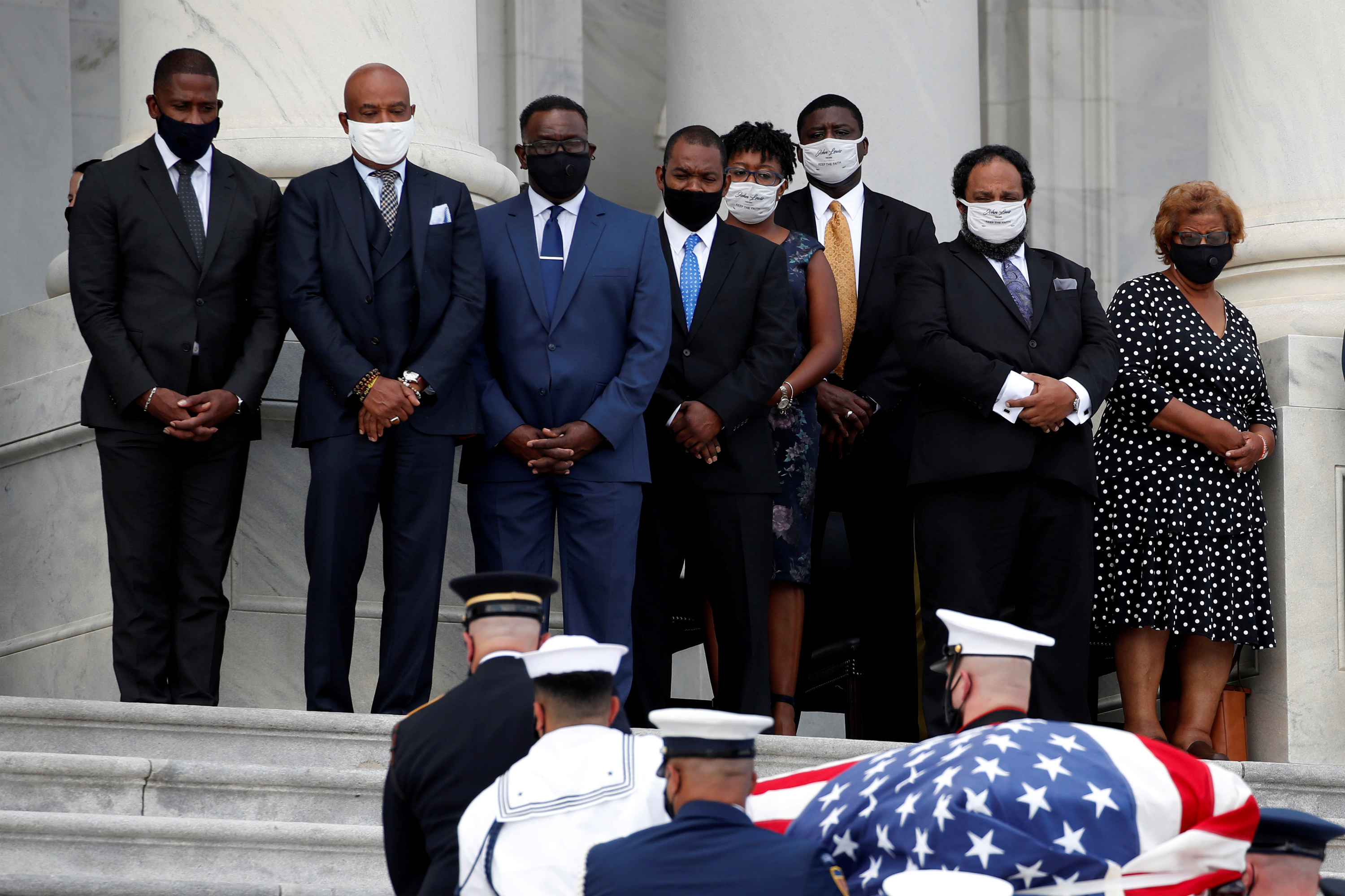Several people wearing masks watch as a casket is carried by members of the military up a staircase