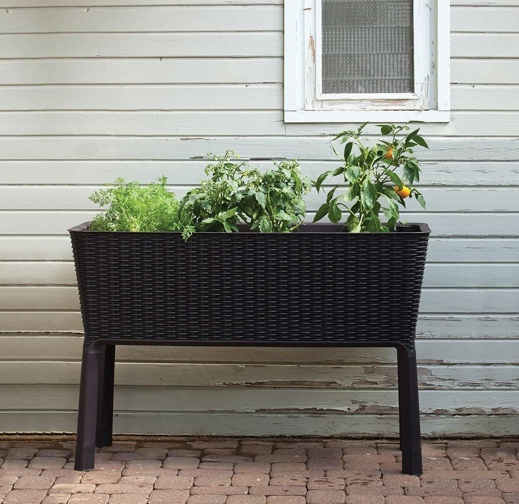 a raised dark brown woven garden bed