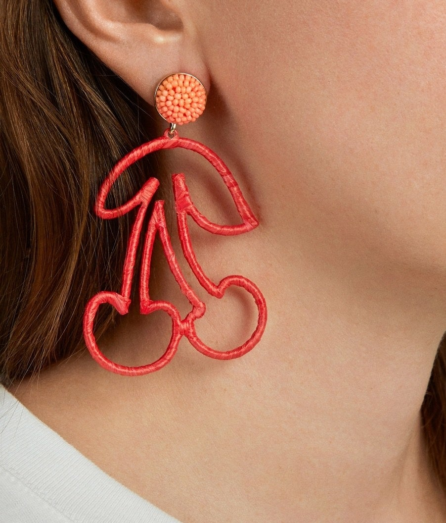 A model wearing the large drop earrings, which have an orange beaded post and a red raffia outline of a cherry