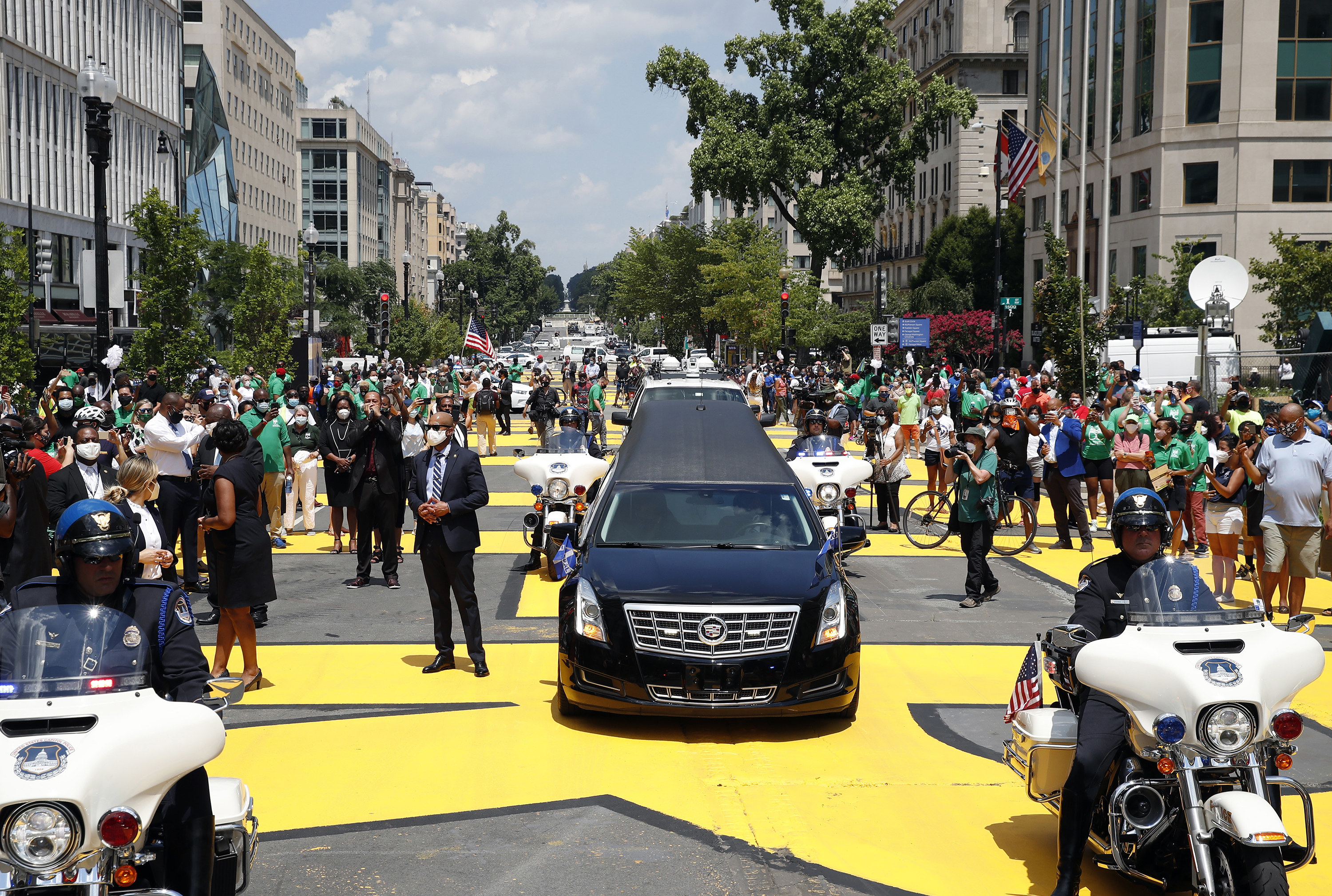 """People spill into the street to surround a motorcade, including a hearse; big yellow letters on the street spell out """"Black Lives Matter"""""""