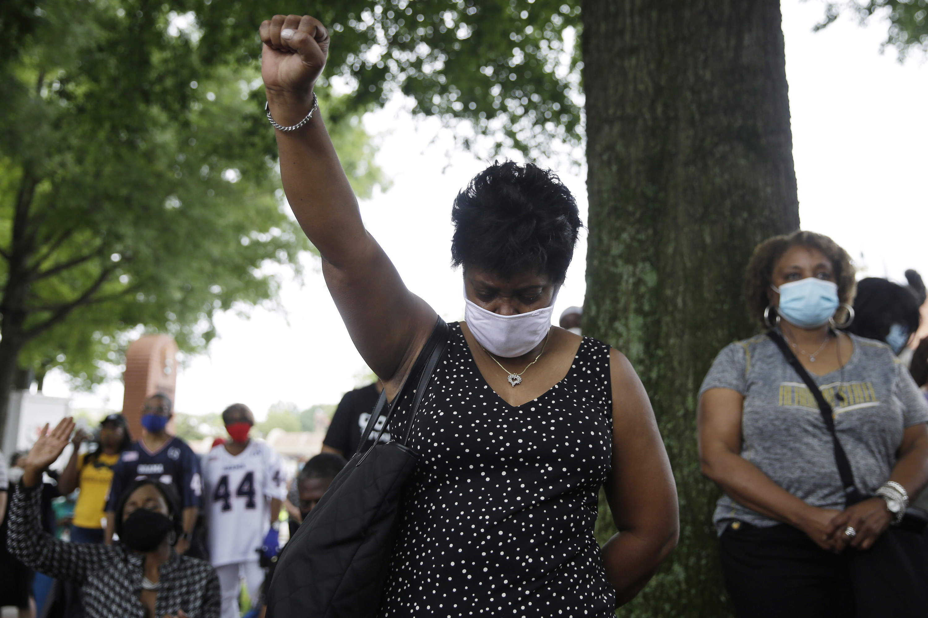 A black woman wearing a black dress and white mask looks to the ground and raises her fist