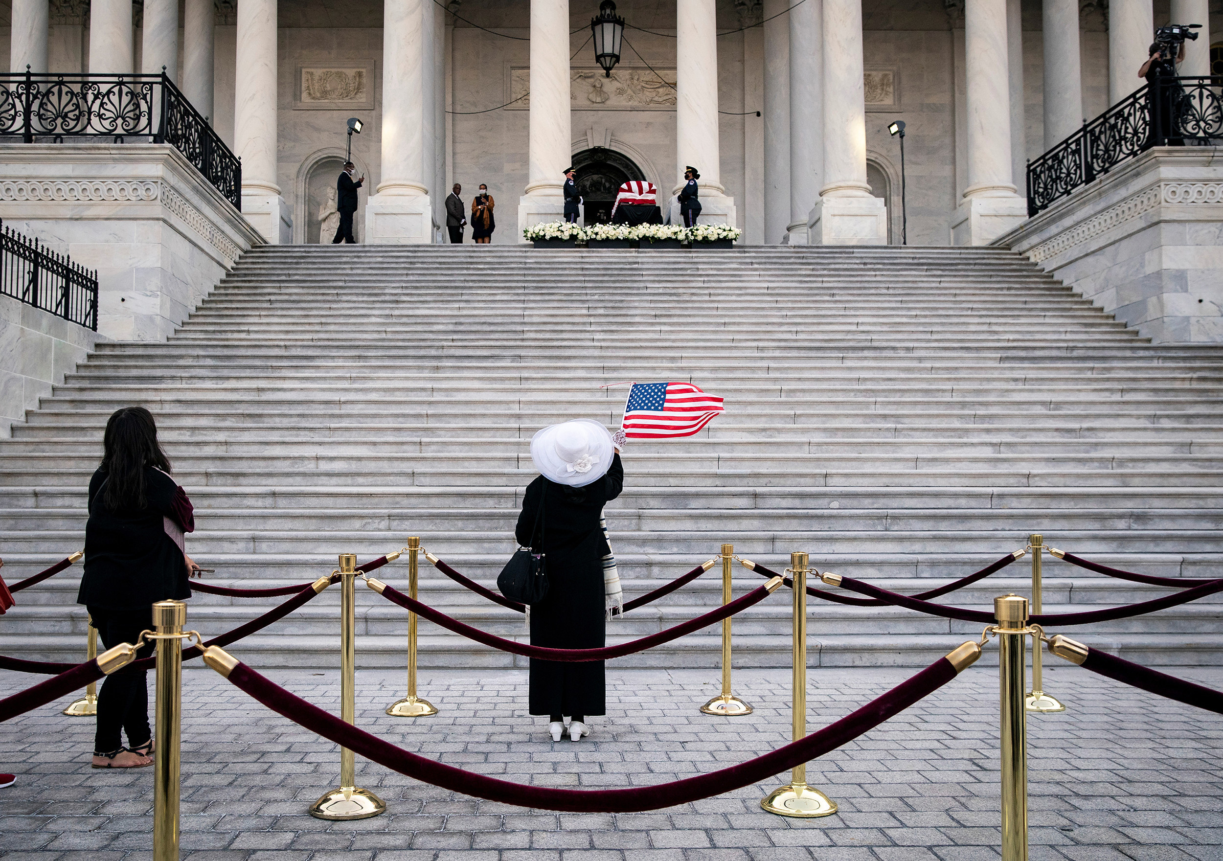A woman dressed in black, with a white hat and white shoes, raises a US flag at the steps of the Capitol, looking up at John Lewis's flag-draped casket at the top of the stairs