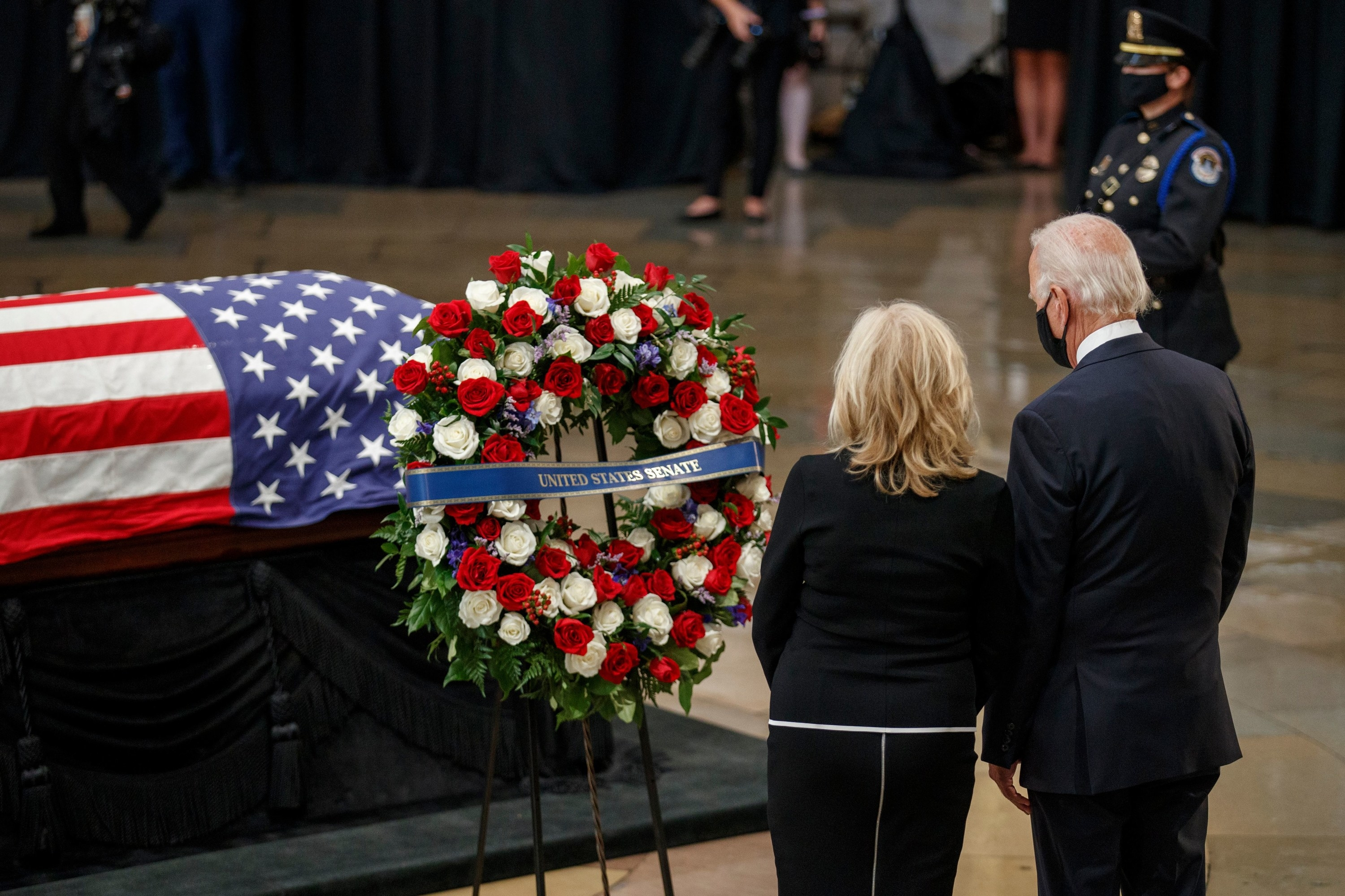 """Joe and Jill Biden stand by the flag-draped casket; a wreath of roses has a sash that reads """"United States Senate"""""""