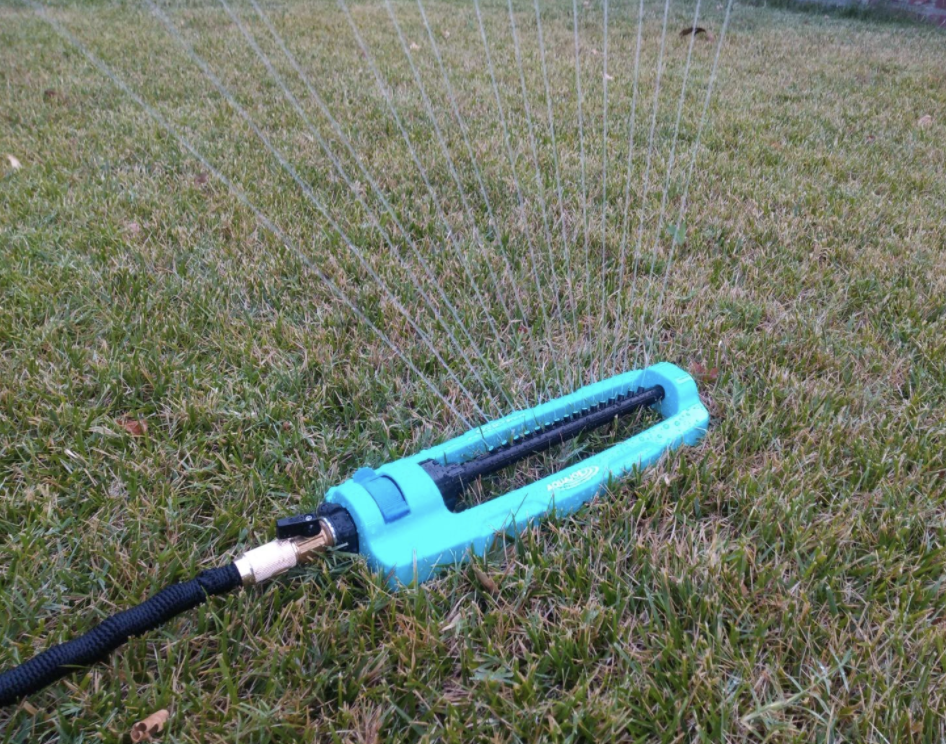 a blue long metal sprinkler attached to a house in a lawn