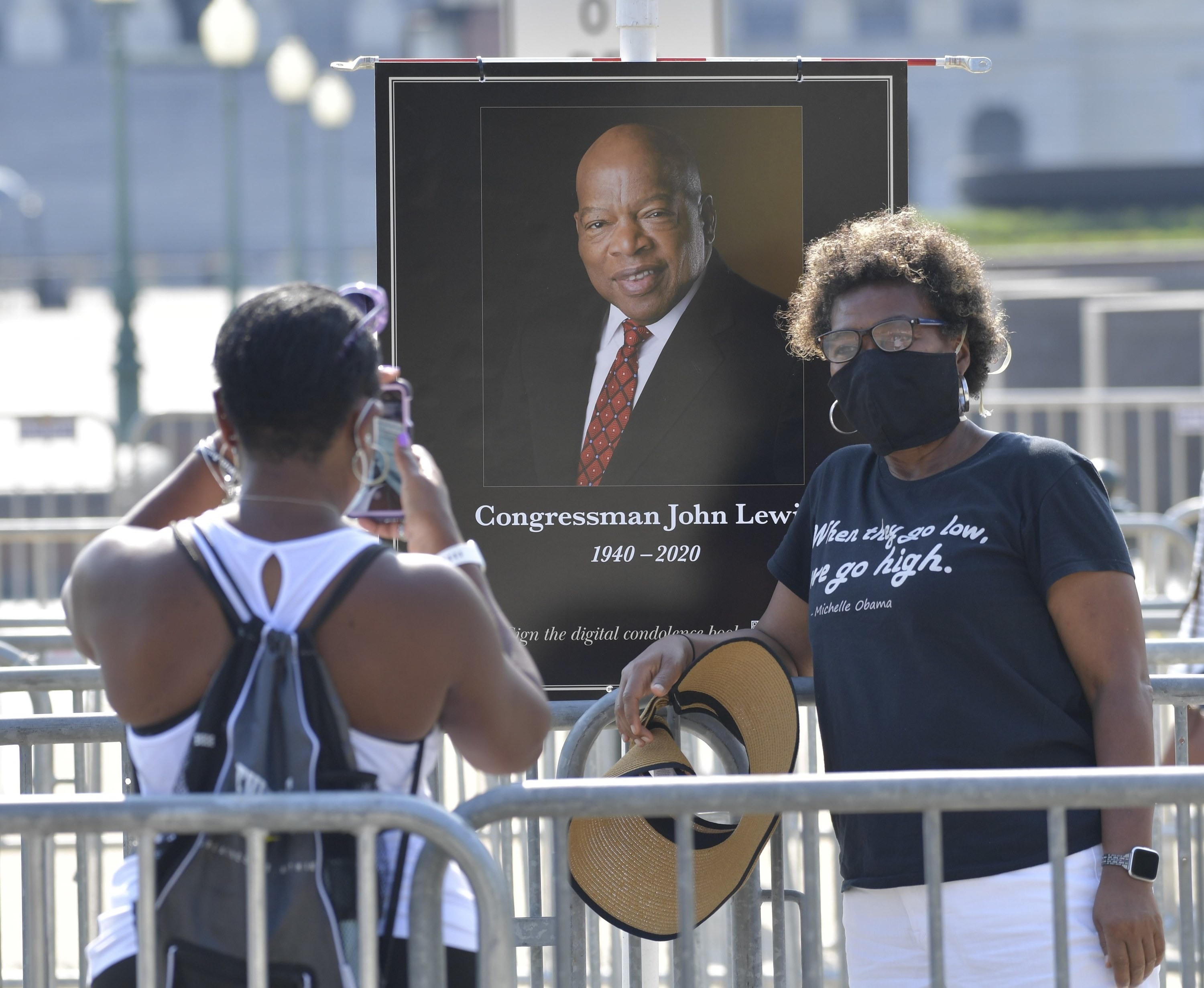 """A woman takes a picture of another woman, who wears a mask and stands in front of a framed picture of John Lewis; her T-shirt reads a quote from Michelle Obama, """"when they go low, we go high"""""""
