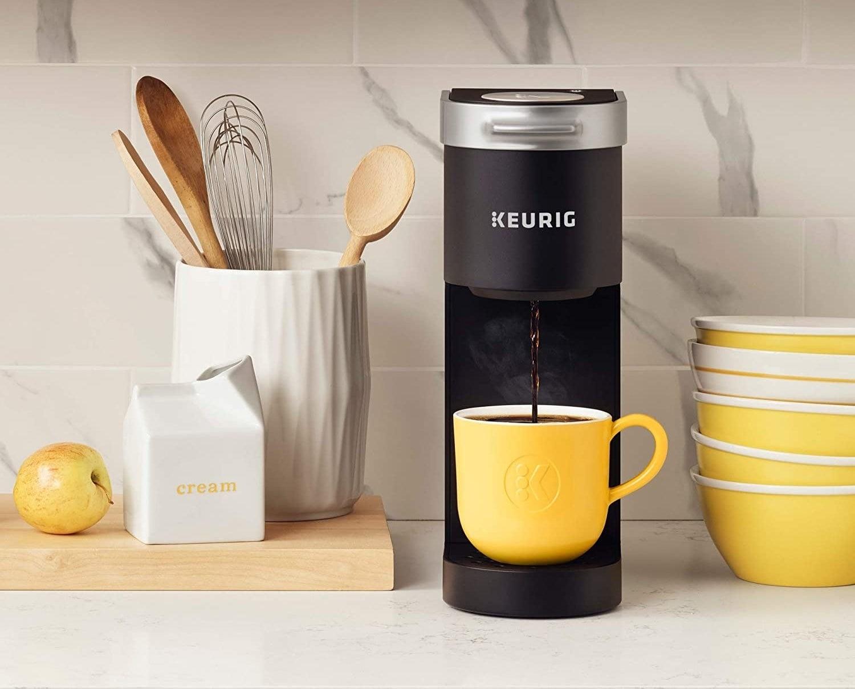The slim machine dispensing coffee into a mug