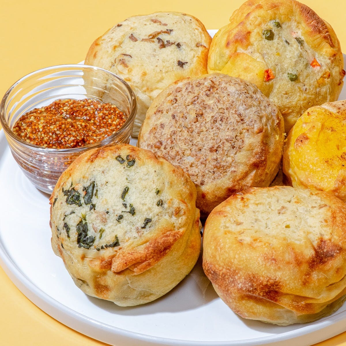 An assortment of different knishes filled with ingredients like spinach, apple, and potato from Yonah Schimmel.