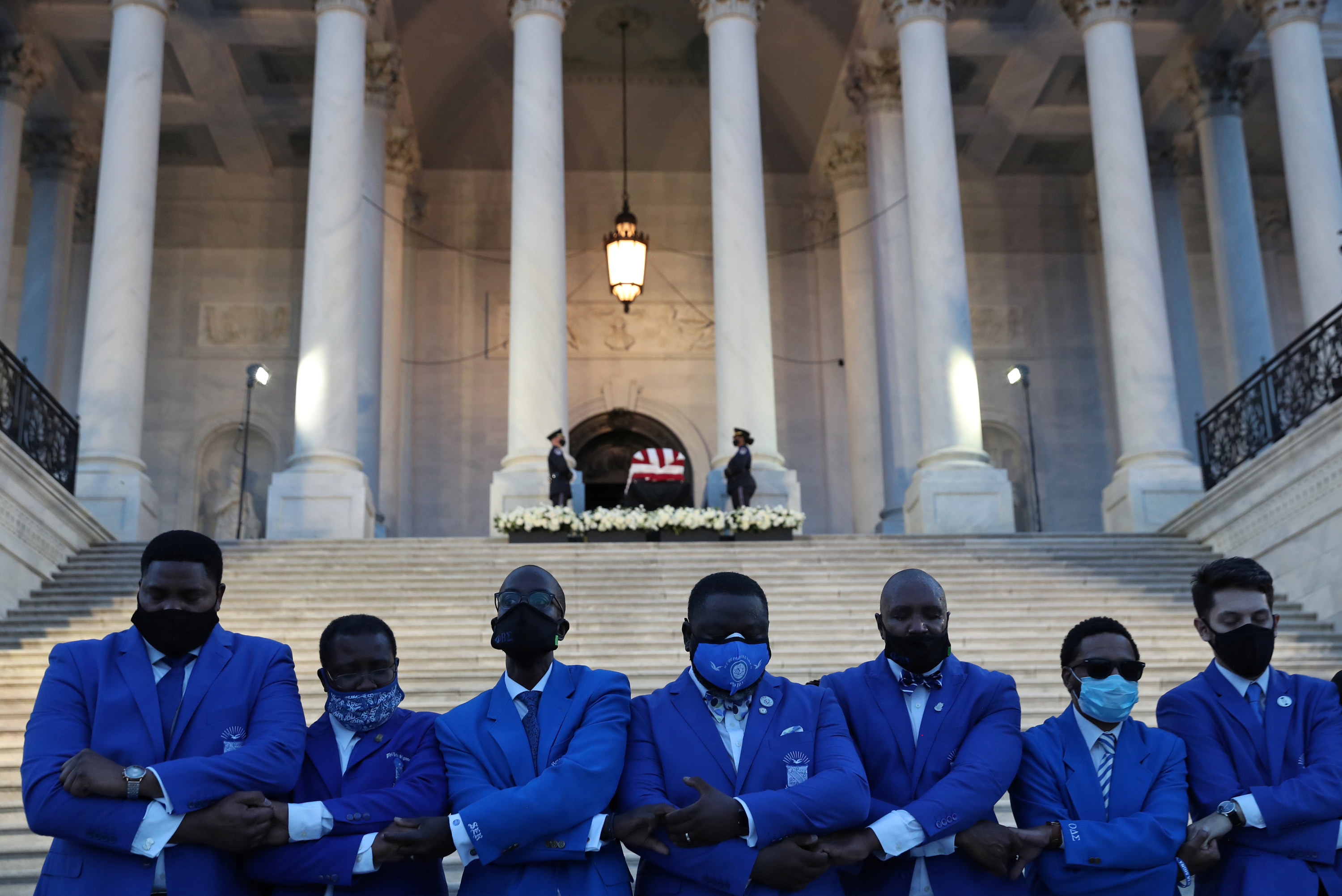 Men in blue suits, all wearing masks, stand shoulder to shoulder and hold hands outside the Capitol in Washington, DC