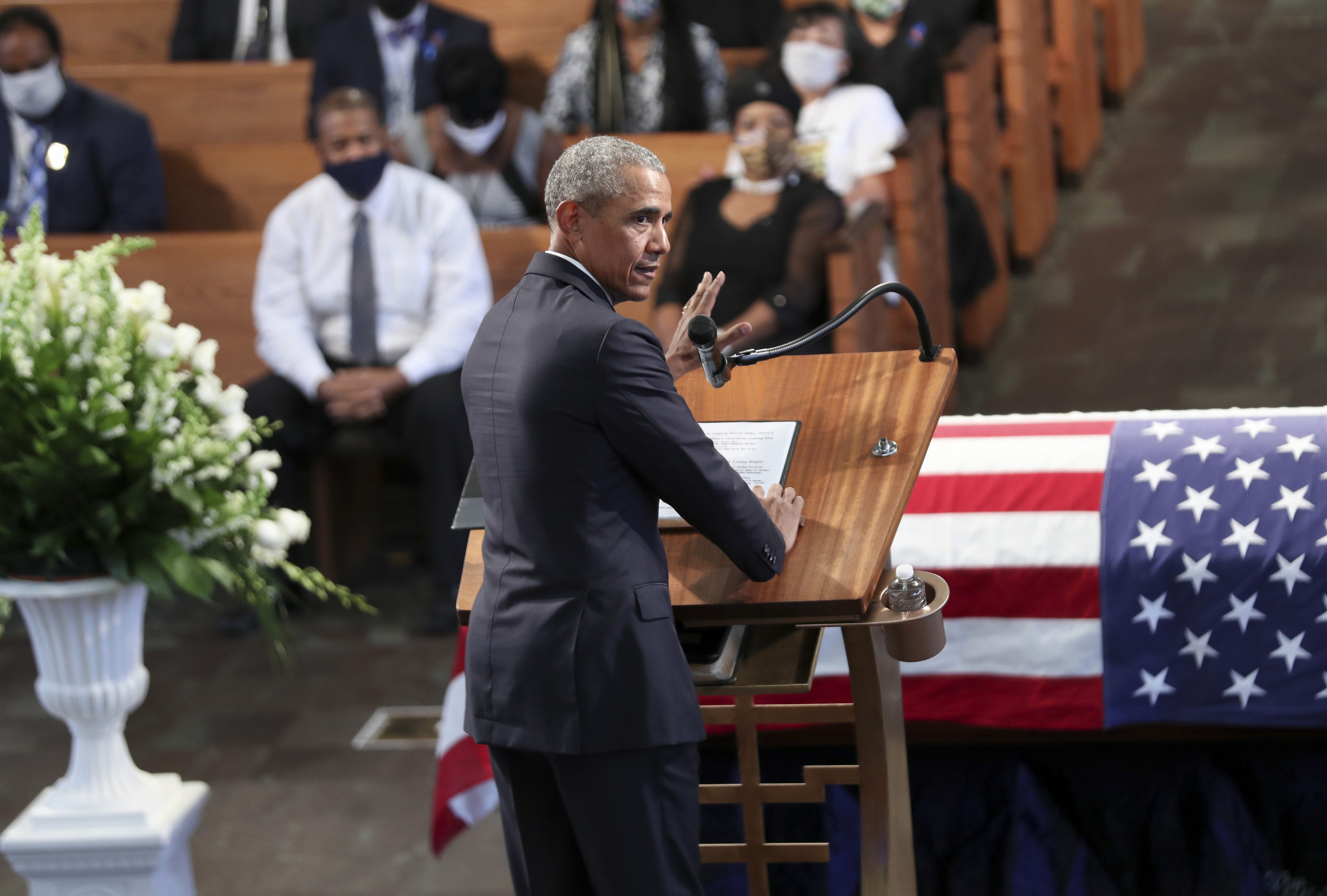 Obama at the lectern in front of the flag-draped coffin of John Lewis
