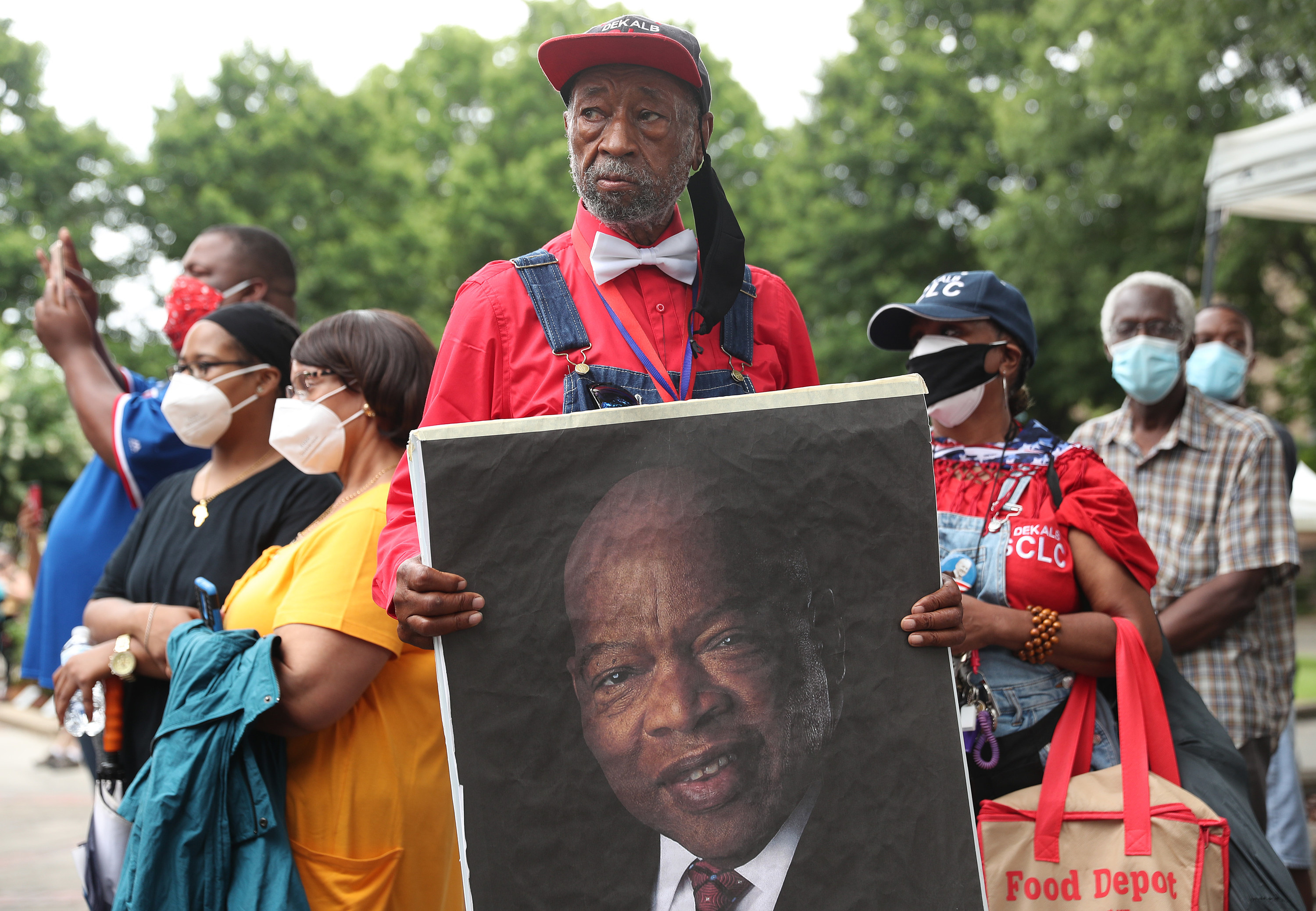 A man holds up a large image of John Lewis