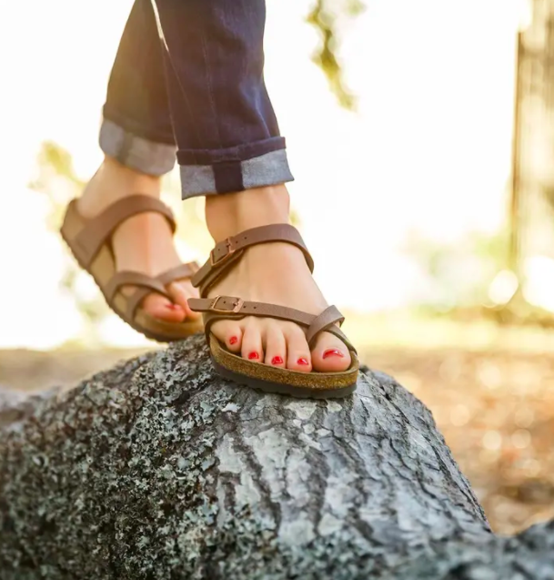 A model wearing the brown shade of sandal