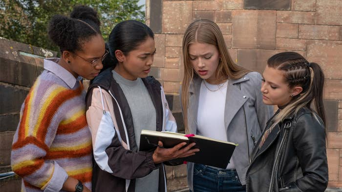 Four woman stand while looking at a book in a still from Get Even.