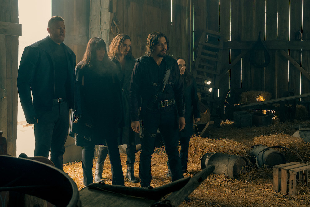 The cast of The Umbrella Academy stands in a barn.