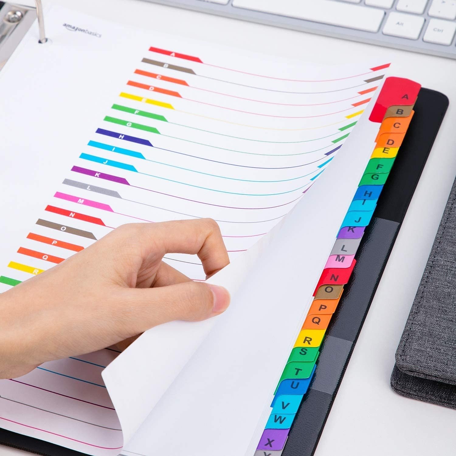 A hand holds the cover page of an index sheet with coloured and lettered corresponding tabs