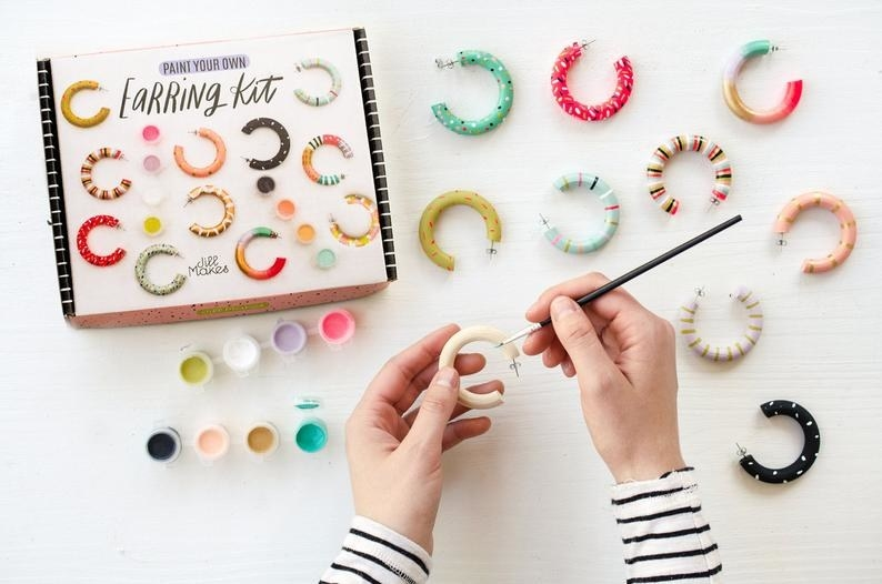 Hands using the brush to paint a chunky wooden hoop, plus examples of earrings painted in the pastel purple, green, teal, peach, pink, gold, black, and white color palette