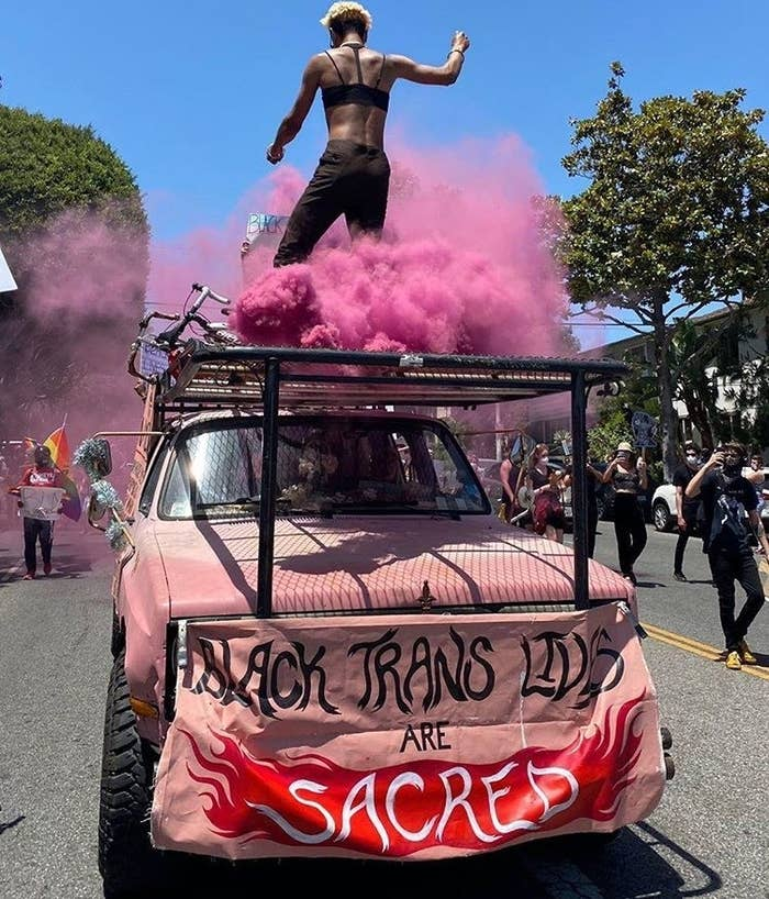 The artist Huntress Janos dances on top of the pink truck known as Pablita.