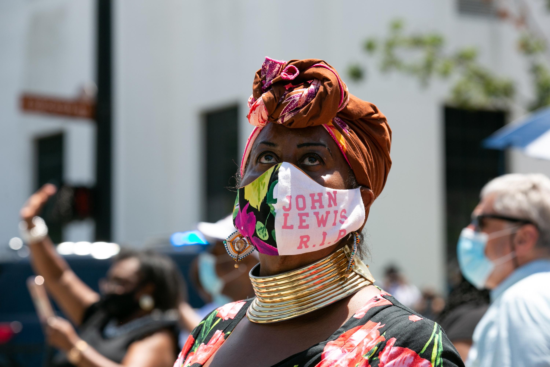 "A woman wears a mask that says ""John Lewis RIP"""