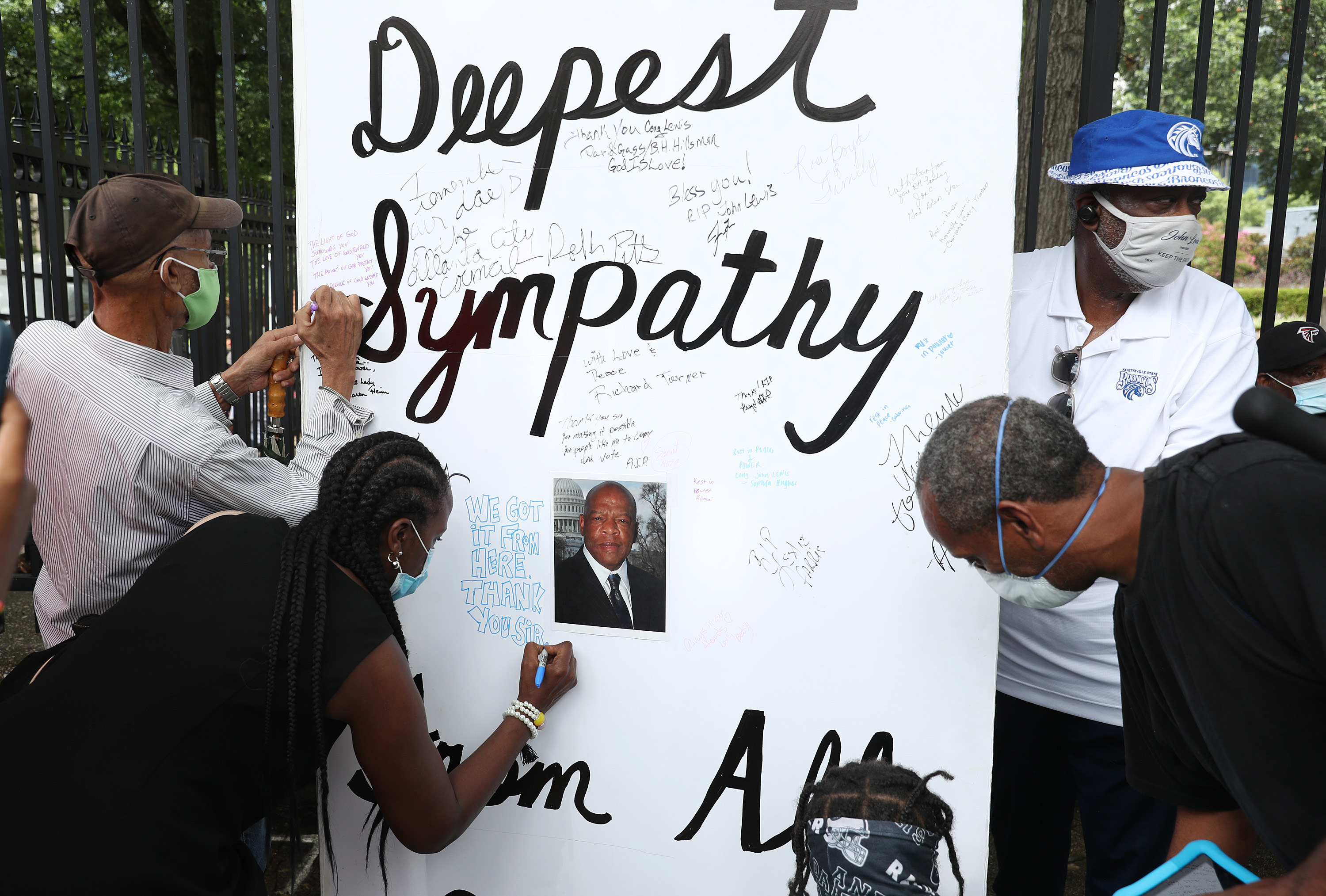"""A large poster board for John Lewis reads """"Deepest Sympathy"""" as people use markers to write notes"""