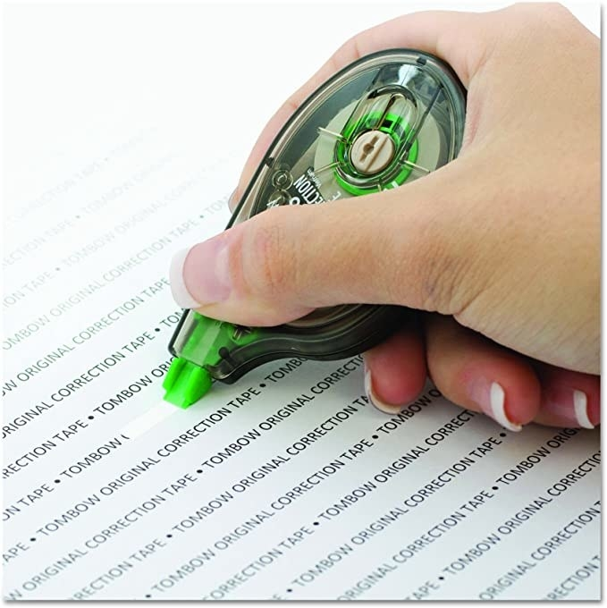 A hand uses corrective tape on a document