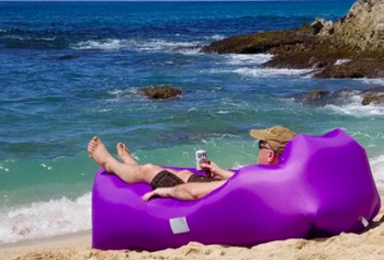 Reviewer sits in purple inflatable lounger while drinking a beer on the shore