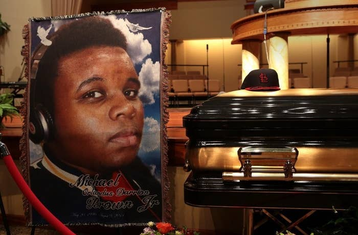A large poster of Michael Brown sits next to his casket, which has a St Louis Cardinals cap placed on top