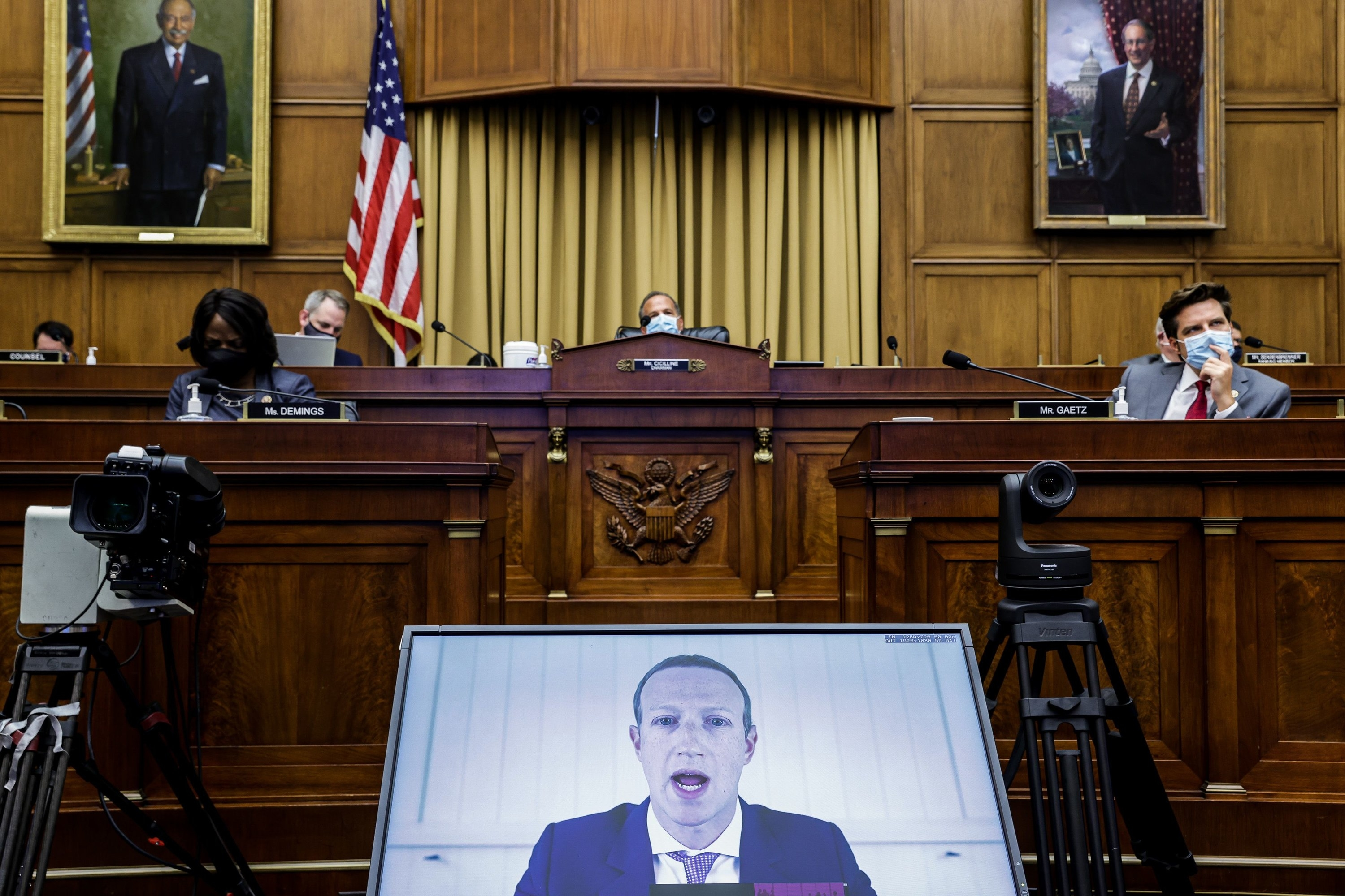 Mark Zuckerberg appears in a screen at the bottom; above, members of the House subcommittee sit and listen