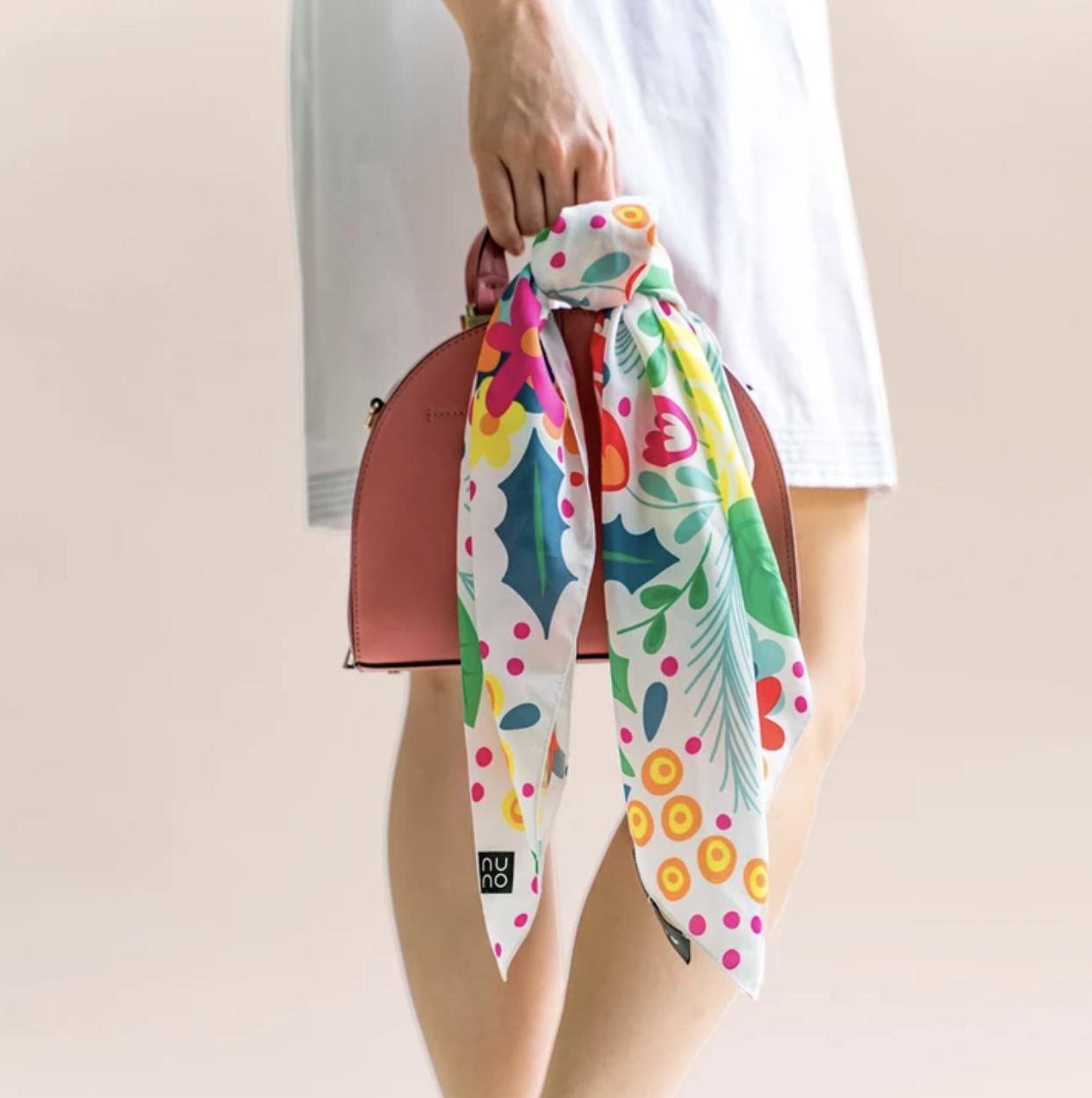 The colorful floral silk scarf tied on a handbag