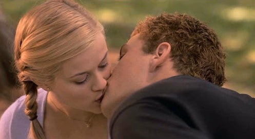 Annette and Sebastian kissing in the park.