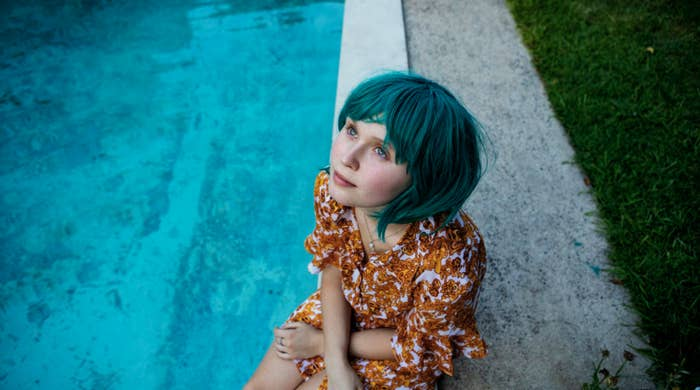 A girl in a short, bright wig sits by a pool, looking peacefully up at the sky