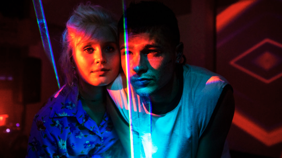 A young man and woman are close beside each other, technicolour lights projected onto them