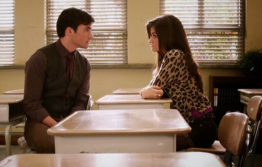Aria and Ezra talk in a school classroom