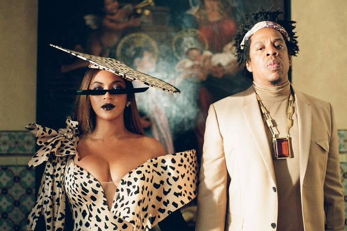 Beyoncé wears an animal print dress and hat next to her husband, Jay-Z, who wears a tan-colored suit jacket and turtleneck