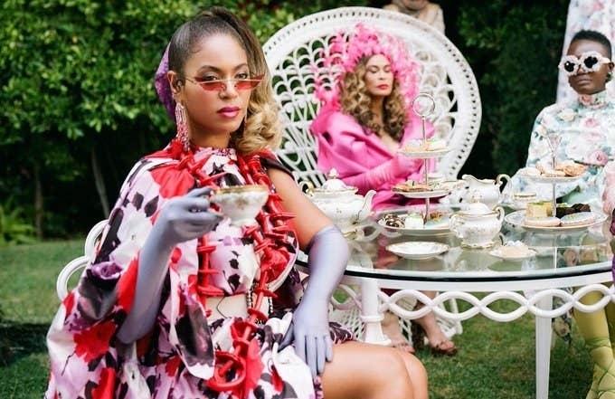 Beyoncé sits at a backyard table, which is filled with teapots and cookies for a tea party, and raises a teacup